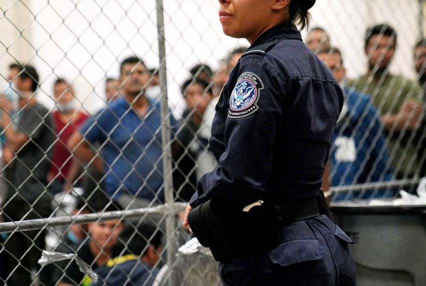 A U.S. Customs and Border Protection agent monitors adult male detainees at a Border Patrol station in McAllen during a visit to the facility by Vice President Mike Pence.