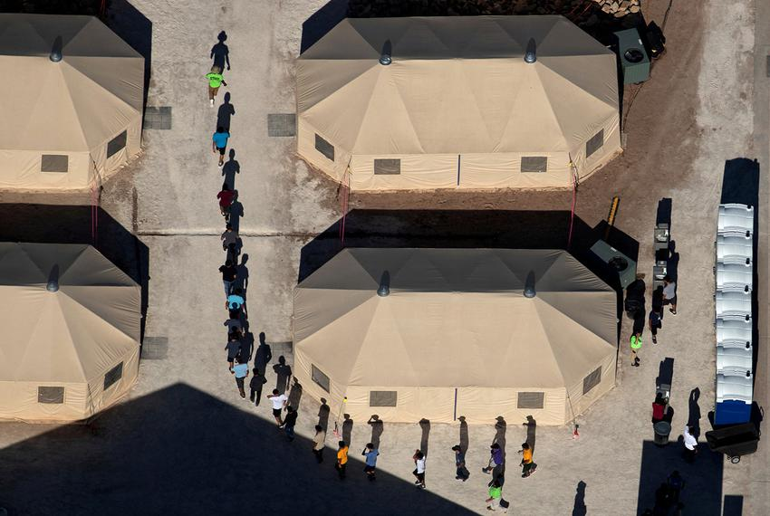 Immigrant children are led by staff in single file between tents at a detention facility next to the Mexican border in Tor...