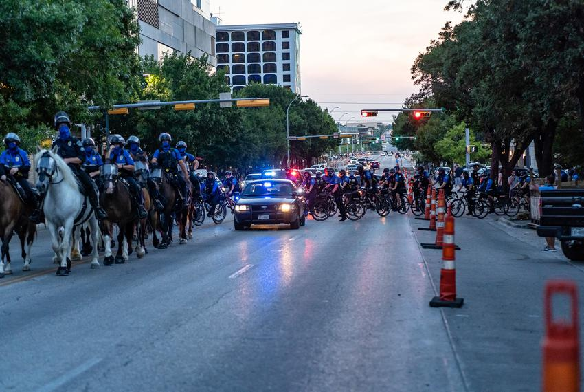 Mounted officers from APD ride towards protesters on the corner of Fourth St. and S. Congress Ave in downtown Austin on Au...