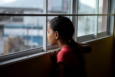 Elibette Trujillo looks out of a window at Casa Indi in Monterrey, Nuevo Leon on Aug. 6, 2019. Elibette migrated from Honduras with her mother Nora Valdez. The pair are waiting at the shelter until their asylum hearing.