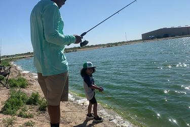 Joseph Norman fishes with his son at a saltwater pond in Imperial.
