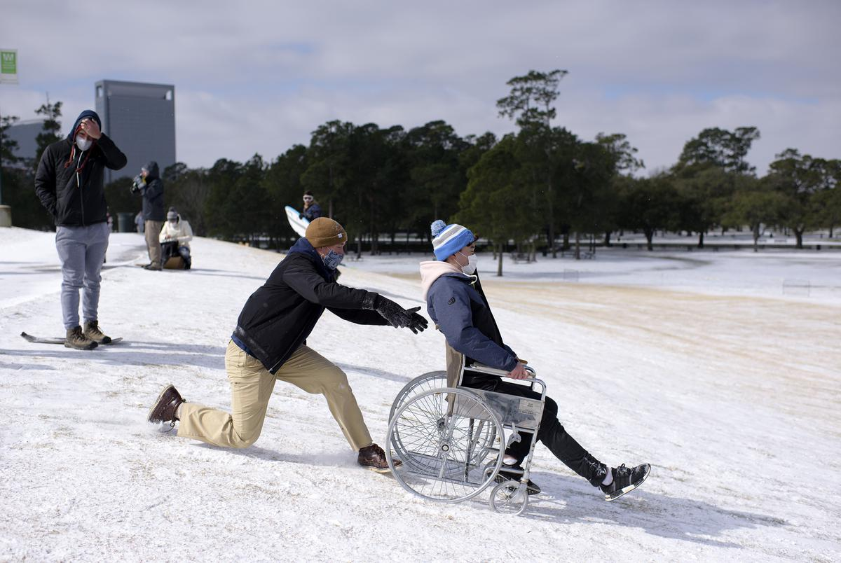 Sledders use a wheelchair to go down a hill at Hermann Park in Houston on Feb. 15, 2021.