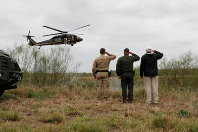 President Donald Trump and U.S. Customs and Border Protection agents salute a U.S. Border Patrol helicopter as it flies over the Rio Grande during his visit to the U.S.-Mexico border in Mission on Thursday, January 10, 2019.