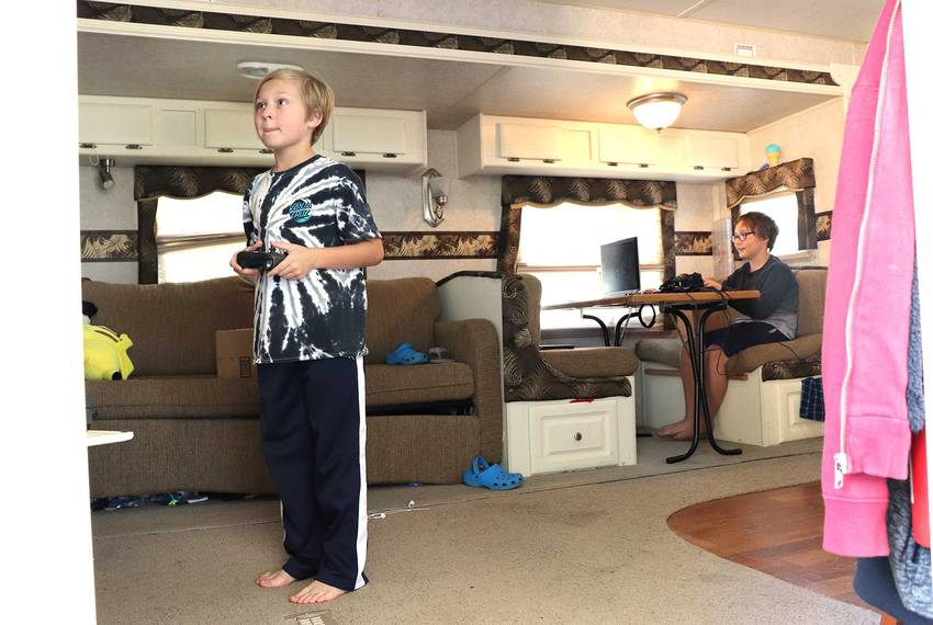 Ashton Eichberger (left) and his older brother, Aiden Eichberger (right), play video games together in the RV that became their temporary home after Harvey flooded their house in Friendswood, Texas.
