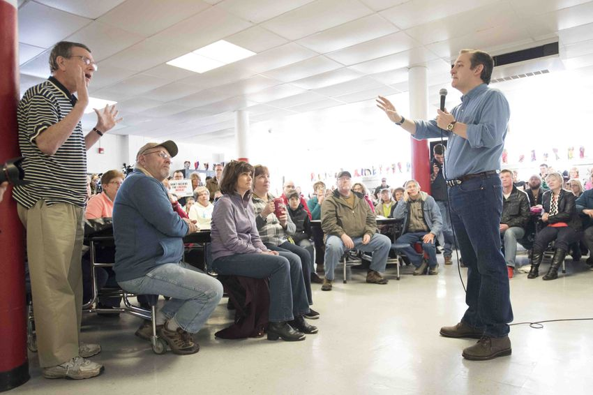 Ted Cruz talks with a man about his plan for health insurance during a stop at South Hardin Middle School in Hamlin, Iowa on Jan. 30, 2016.