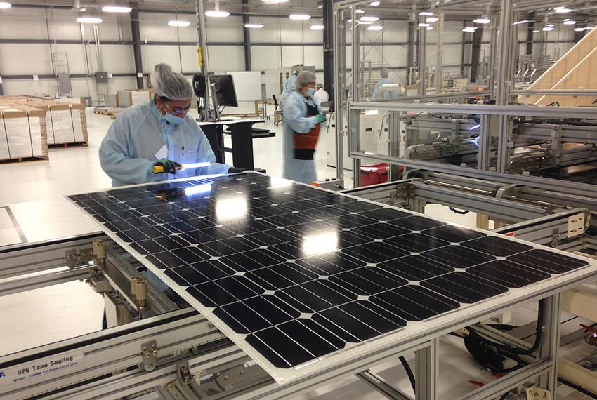 A worker at Mission Solar in San Antonio inspects the protective coating of a fully assembled solar panel for bubbles that c…