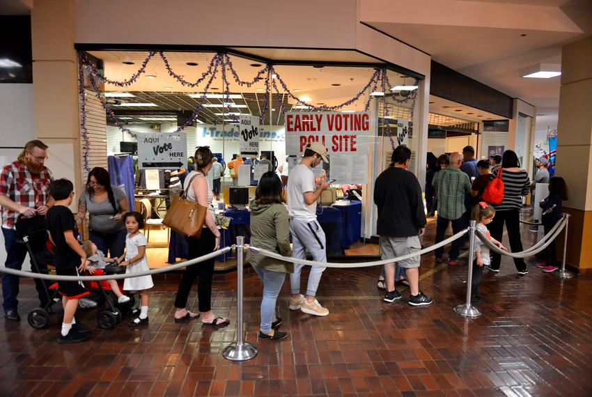 A long line of voters wait to cast their ballots at the Wonderland of the Americas Mall in San Antonio late Friday afterno...