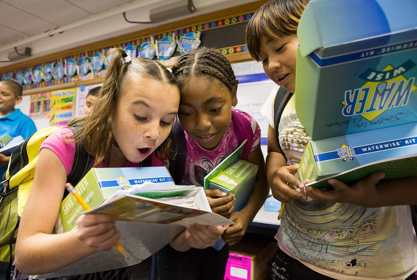 Three students at Bayless Elementary in Lubbock, Texas, consult a water usage chart after being presented with water conserv…