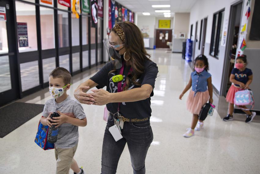 """Kindergarten teacher Mrs. Hogan instructs students to make a """"bubble"""" of room between other students on the first day of in-…"""