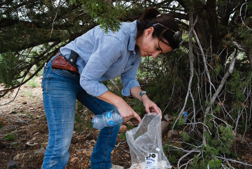 Hudspeth County Administrator Joanna Mackenzie picks up water bottles and a burrito left behind along a trail frequented thr…
