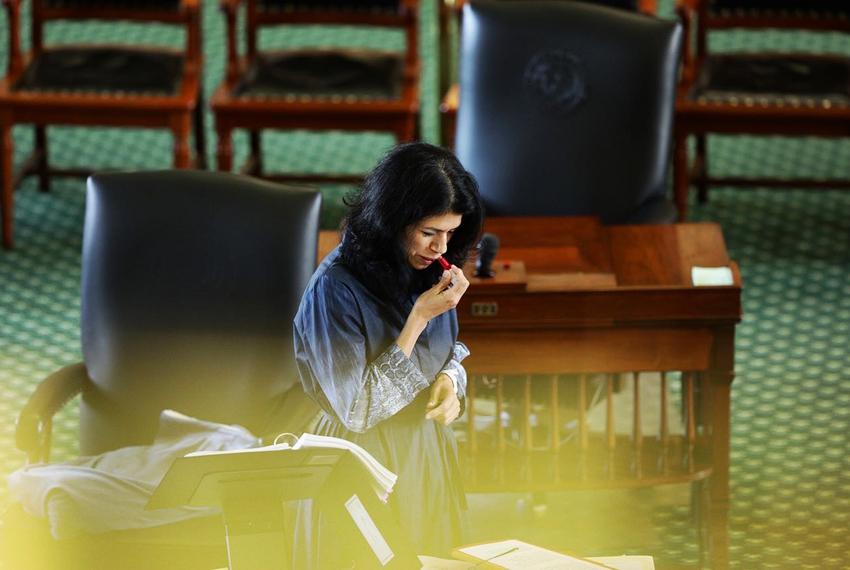 State Sen. Carol Alvarado, D-Houston, applies lipstick in her fifteenth hour of filibustering against Senate Bill 1 on Aug. …