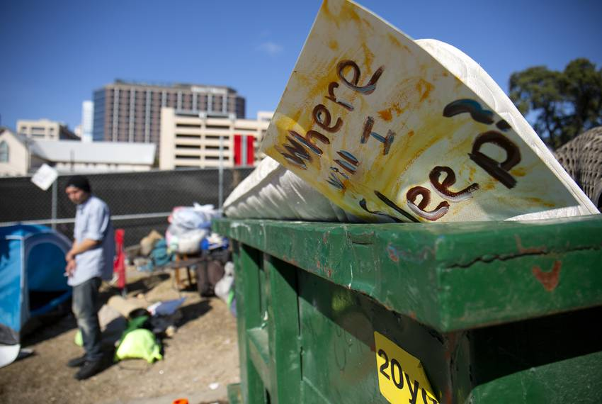 A discarded sign and mattress sit in a dumpster in downtown Austin after city crews cleaned up homeless encampments on Nov...