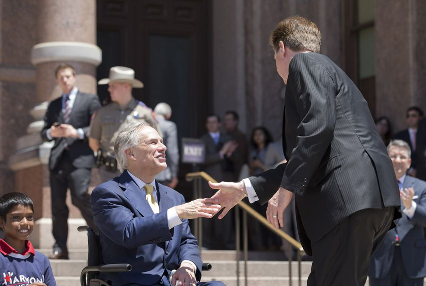 Gov. Greg Abbott and Lt. Gov. Dan Patrick shake during a joint appearance at Texas Charter School rally April 29, 2015.