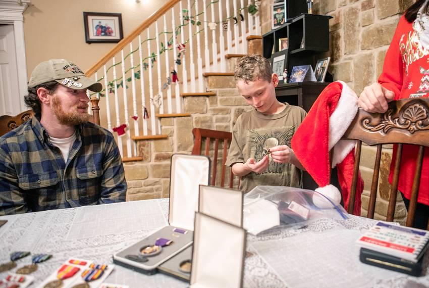 Josh Raines (left) and his son Tristan go through the combat veteran's medals in their dining room. Raines, a medical mari...