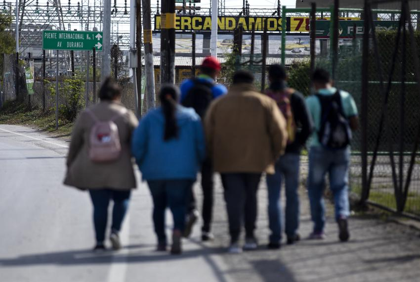 A small group of migrants walk down Libramiento Manuel Perez Treviño in Piedras Negras. The group was recently released fr...