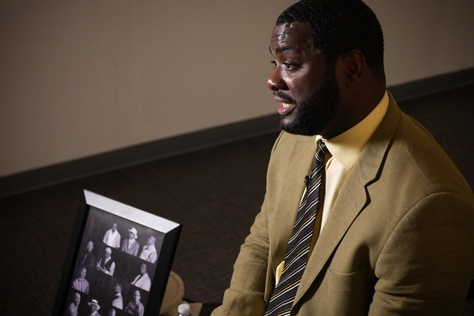 Christopher Scott, wrongfully convicted of murder, tells his story next to a photo of fellow exonerees in a Dallas office in July 2017.