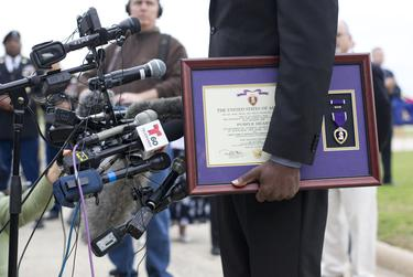 Chief Warrant Officer Christopher Royal, wounded in the November 2009 Fort Hood shootings, holds his Purple Heart while talking to the media on April 10, 2015.