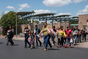 Central American asylum seekers walk to the nearby Catholic Charities Humanitarian Respite Center after being dropped off at the McAllen bus station, on August 2, 2018.