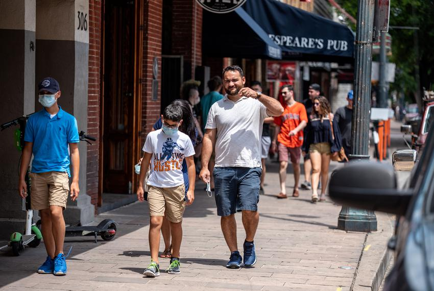 People walk down the sidewalk in downtown Austin on May 23, 2020.
