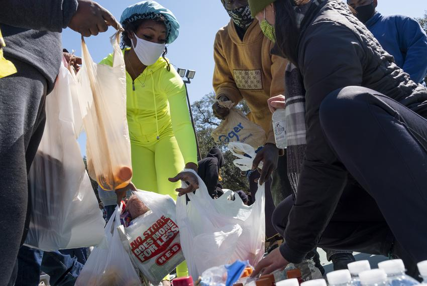 Tenisha Conway, in green, picks up supplies at Kelly Village, a supply distribution site, on Feb. 19, 2021, in Houston.