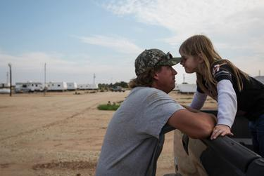 Troy Chamberlin plays with his 5-year-old daughter, Elizabeth, after returning to the RV lot at Custom Touch Village, a so-called man camp established to house workers in West Texas' shale boom. He recently moved to Texas from Colorado, where he worked in corrections.