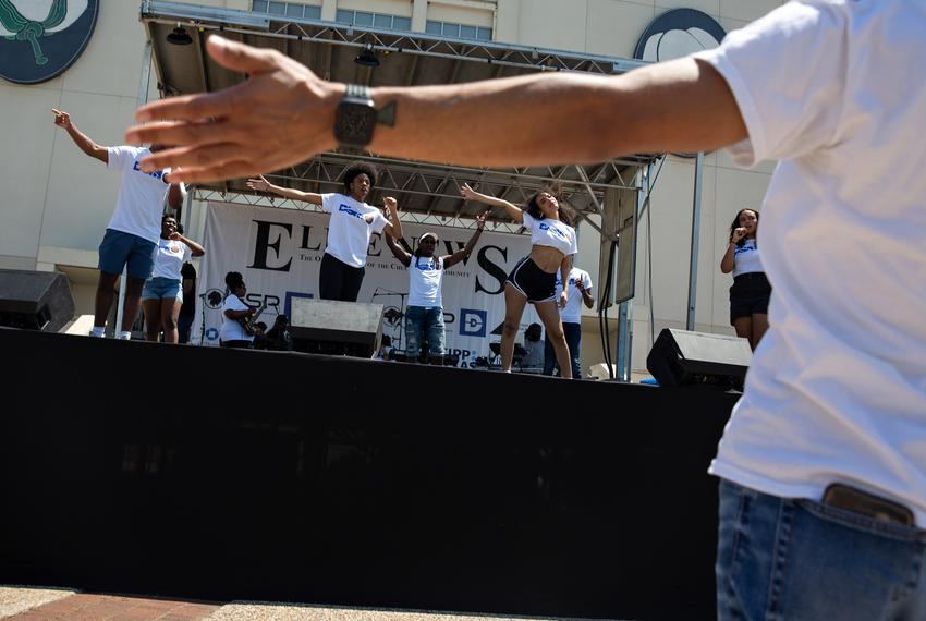 Dallas Summer Musicals director of education and community partnerships Devon Miller leads the group in a run through perfor…