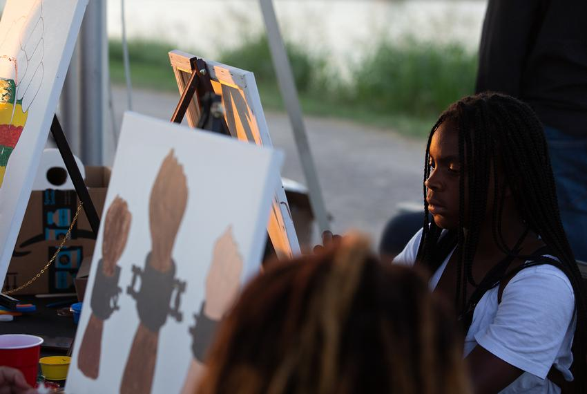Trineese Potter paints at the Creative Tingz shop stand during the I Am Juneteenth festival at the Panther Island Pavilion i…