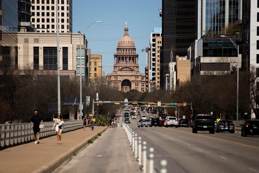 Pedestrians walk across the South Congress bridge with the Capital in the background in Austin on March 3, 2021.
