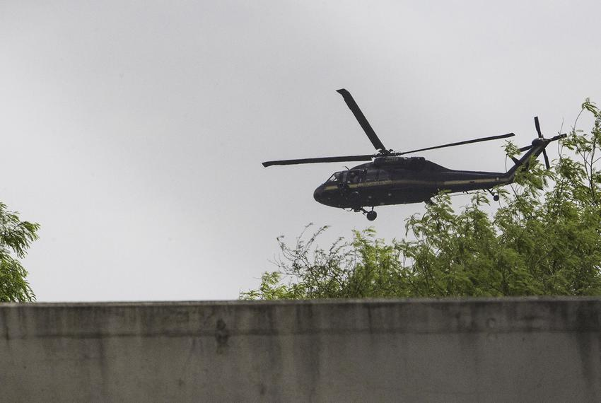 A Department of Homeland Security Blackhawk helicopter flying near Hidalgo swoops low over the Rio Grande above the border...
