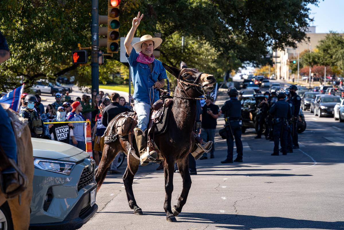 A man rides a donkey past fellow supporters of President-Elect Joe Biden, as Biden Supporters gather at the Texas State Capitol to celebrate his victory in the 2020 Presidential Election.