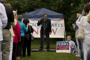 A New Hampshire voter with a recycled 2012 Perry for President sign listens to the governor speak in Stratham on Saturday.