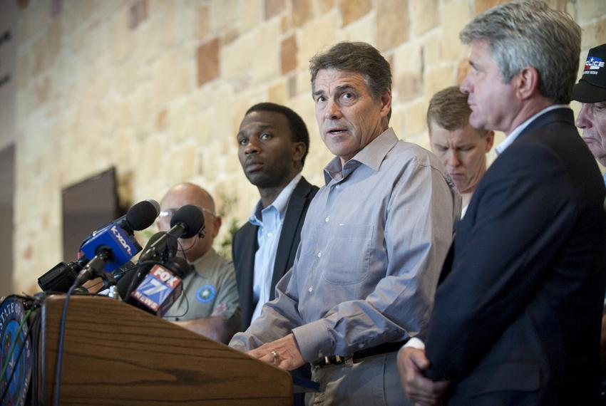 Texas Gov. Rick Perry, c,  answers question from citizens and the media in Bastrop after his return from a campaign trip to …