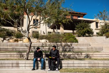 University of Texas at El Paso students Damian Blancarte, 22, left, and Enrique Martinez, 23, sit next to each other in the campus quad in El Paso on Dec. 2, 2020.