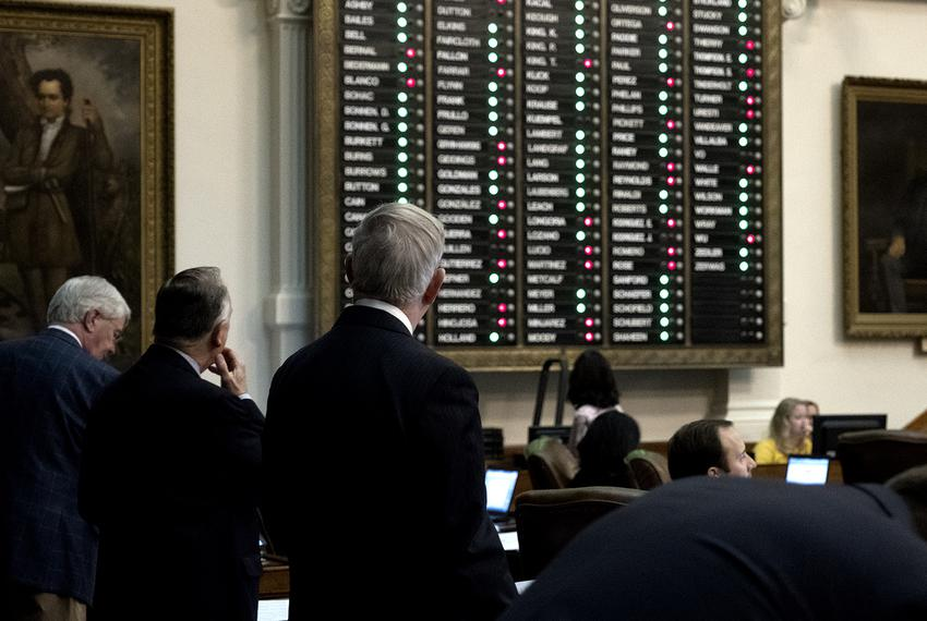 Representatives look at the board as a vote is taken on a bill amendment thatwould require schools to provide single-stall …