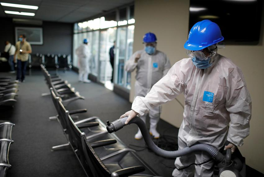 Workers spray sanitiser at the Ilopango International Airport as a preventive measure against the coronavirus disease (COV...