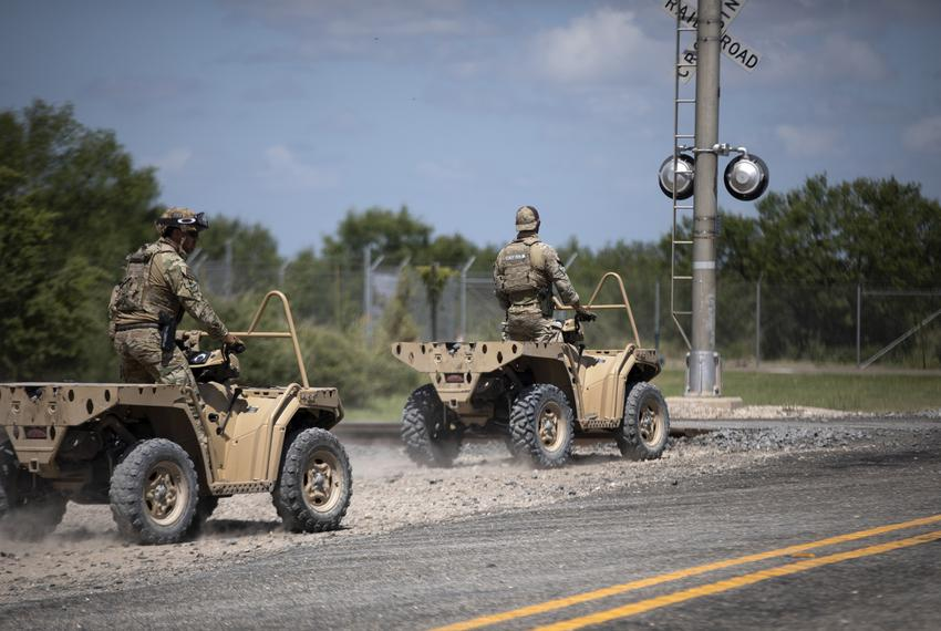 Texas Department of Public Safety officers ride all-terrain vehicles near a train depot in Spofford on Aug. 25, 2021. The of…
