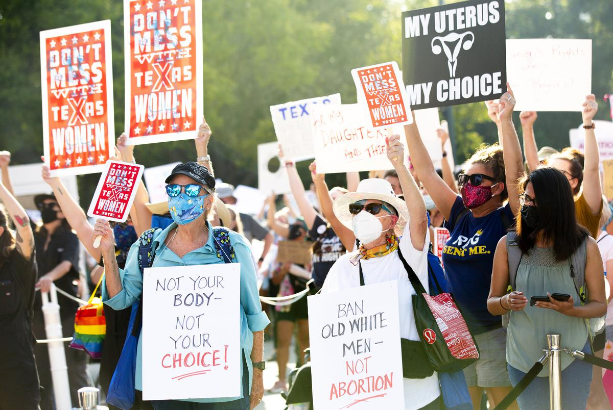 Dyan Lee and Judy Kajander hold and wear signs as they listen to speakers during the Women's March ATX at the Texas Capitol in Austin, Texas, on Saturday, Oct. 2, 2021. Thousands of people attended the rally in support of womenís reproductive health and access to safe abortions.