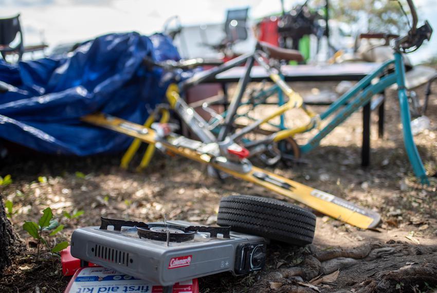 A propane burner sits near bike parts near a former homeless encampment on Riverside Drive on Sept. 28, 2021 in Austin. Many…