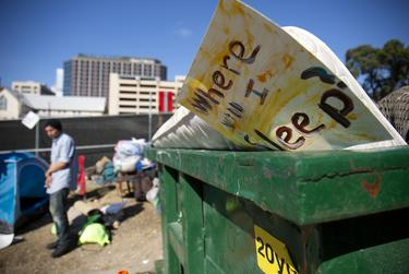 A discarded sign and mattress sit in a dumpster in downtown Austin after city crews cleaned up homeless encampments on Nov. 4, 2019.