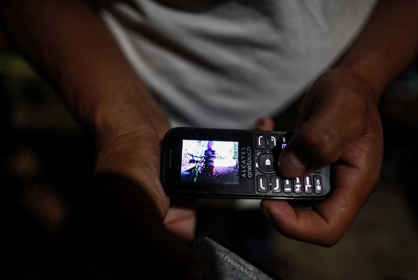 David Xol shows a picture of his son Byron that he keeps on his cellphone. Byron is in a shelter in Baytown.