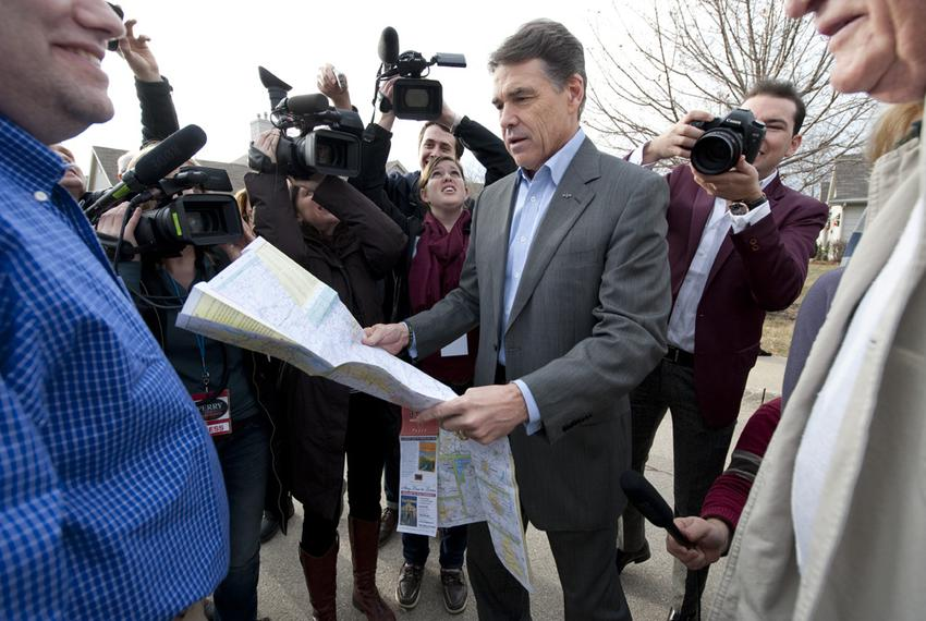 Gov. Rick Perry unfolding a Texas map on Dec. 31, 2011, to show Des Moines residents where his hometown of Paint Creek is lo…
