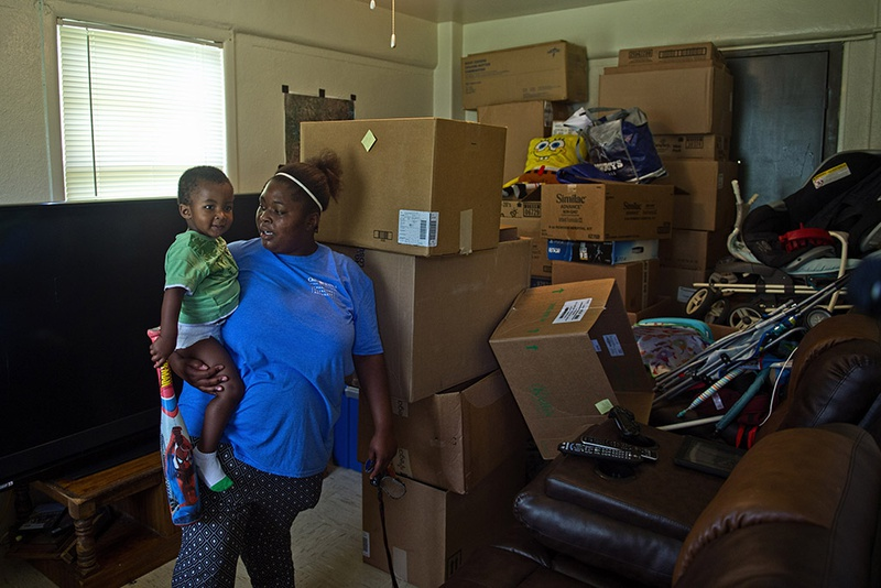 D.N. Leathers Public Housing Complex resident Jasmine Mosley holds her son De' Monei Traylor, 2 in their apartment on September 8, 2016