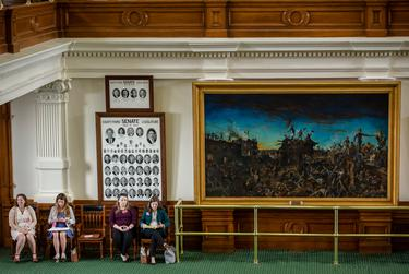 People wait on the Senate floor during session at the state capitol on May 25, 2021.