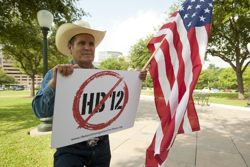 "Hispanic male holds American flag and sign showing his opposition to HB12 the ""sanctuary city"" bill on Capitol grounds May..."