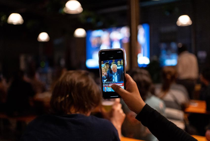 A supporter records Bernie Sanders speech on their cell phone as Sanders' speech is broadcast on television at a Bernie Sa...