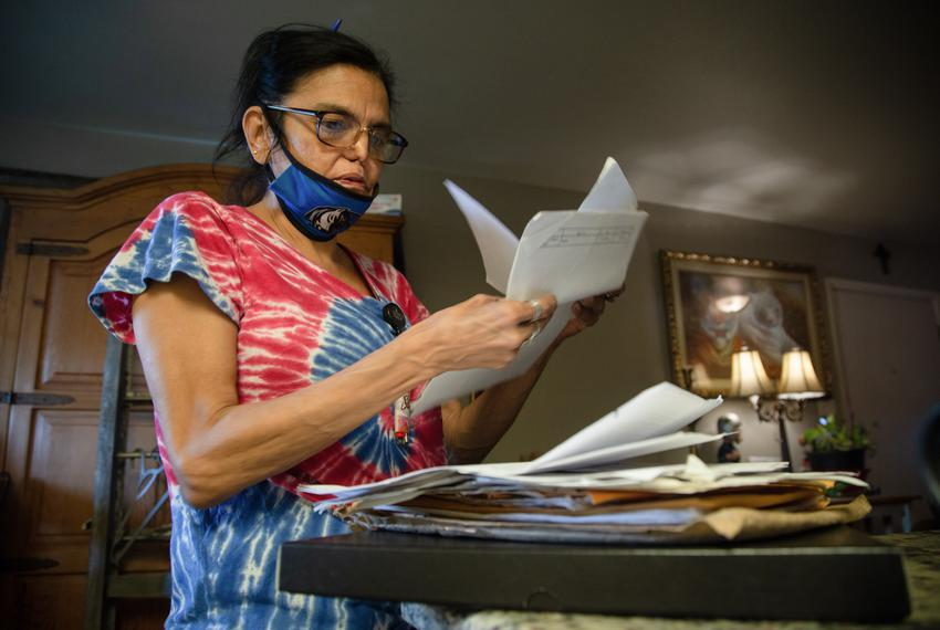 Marcela Ramos looks through stacks of paperwork concerning rental assistance in her home in West-Central Dallas, on May 13, …