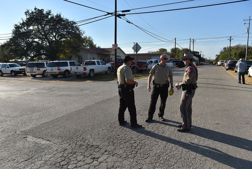 U.S. Marshals speak with a DPS officer in Sutherland Springs after a mass shooting at the First Baptist Church there, on Sunday, Nov. 5, 2017.