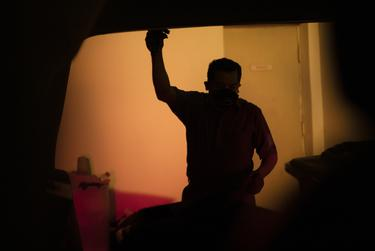 Juan Lopez opens the back door of his Cadillac Escalade ro remove a dead body from the vehicle. Lopez drives to various locations in the Rio Grande Valley to pick up the recently deceased and deliver their remains to funeral homes. July 17, 2020.