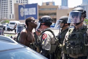 A protester stares down a police officer during a march near downtown Austin. The group gathered to oppose the recents deaths of George Floyd and Mike Ramos. May 30, 2020.