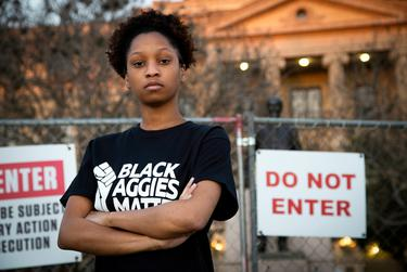 Qynetta Caston, at Texas A&M University, stands in front of a fenced-in statue of former college president Lawrence Sullivan